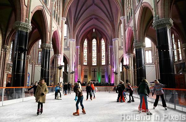 Nederland Gouda - december 2018. Schaatsen in de Gouwekerk. IJsbaan in een oude kerk. De Gouwekerk ( Sint-Jozefkerk ) is een neogotische kruiskerk.