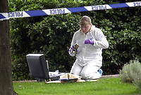 Scenes of crime officer in a white suit dusting for fingerprints after an incident took place in a park. Two men were fighting over a can of beer and one stabbed the other and ran off. The officer is dusting the can. The area has been cordoned off with police barrier tape...© SHOUT. THIS PICTURE MUST ONLY BE USED TO ILLUSTRATE THE EMERGENCY SERVICES IN A POSITIVE MANNER. CONTACT JOHN CALLAN. Exact date unknown.john@shoutpictures.com.www.shoutpictures.com..
