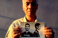 Vann Nath, a painter, holds up his mugshot, taken when he was a prisoner of the Khmer Rouge. He was one of only seven people who survived incarceration in the notorious Tuol Sleng prison.