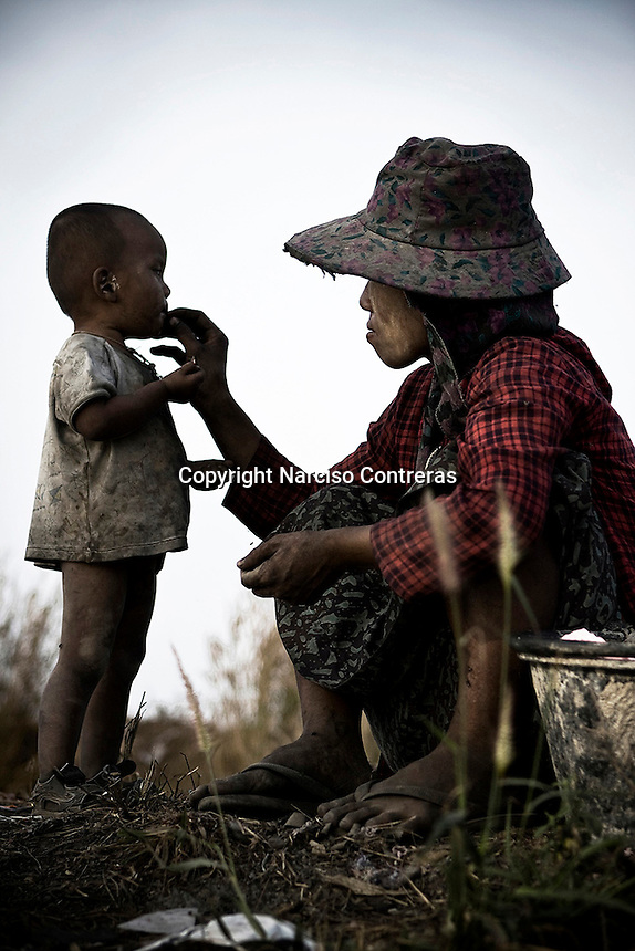 A burmese mother give some food she found in the garbage to her child. Dumpsite Mae Sot, Thailand.