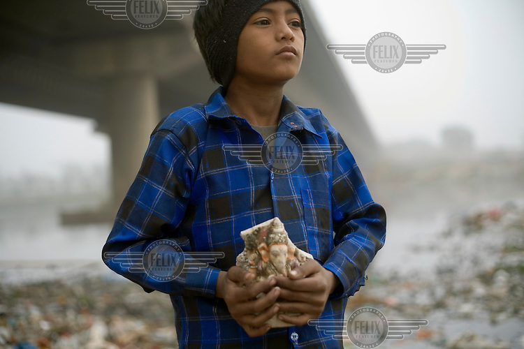 A young ragpicker holding a discarded statue of a Hindu god that has been ritually submerged into the nearby Yamuna River by the Kudsia Ghat. The Yamuna is now so polluted that it can no longer support life. However, there is a whole community still living along the riverbanks here.