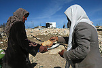 A Palestinian Bedouin man and his wife eat fresh bread next to their tent at Khirbet Umm Al-Khair south the West Bank City of Hebron January 21, 2014. Israeli forces raided Umm al-Khair region several times and notified residents of its decision to destroy their bread ovens, known as taboun, because their smoke reaches the nearby illegal settlement of Karmael. Photo by Mamoun Wazwaz