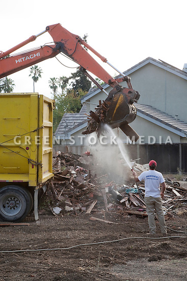 A construction worker spraying water on demolition debris of a single family home. The material is being loaded into a container truck and transported to the Zanker Road Landfill where wood, concrete, gypsum, and metal waste materials will be sorted for recycling. Cupertino, California, USA