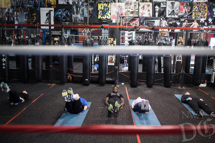 NWA Democrat-Gazette/CHARLIE KAIJO Strightright boxing coach Bernard Oliver leads ab exercises during a boxing class geared towards people with Parkinson's disease, Monday, December 10, 2018 at Straightright Boxing and Fitness Springdale.
