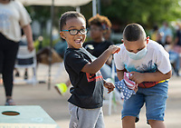 Osafa Hippolyte (left), 3, of Bentonville plays cornhole Friday, June 19, 2020, with Isaiah Palos, 7, of Rogers during a Juneteenth cookout at Lawrence Plaza in Bentonville. Go to nwaonline.com/200620Daily/ to see more photos.<br /> (NWA Democrat-Gazette/Ben Goff)