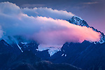 Sunset glow on clouds over glacial peaks of Chugach Mountains, viewed from Glenn Hwy, Southcentral Alaska, Autumn.