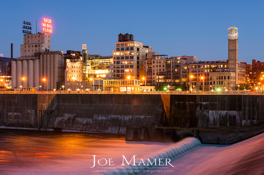 """Downtown Minneapolis, Minnesota at night as seen across the Mississippi River. Saint Anthony Falls, or the Falls of Saint Anthony, located northeast of downtown Minneapolis, Minnesota, was the only natural major waterfall on the Upper Mississippi River. The natural falls was replaced by a concrete overflow spillway (also called an """"apron"""") after it partially collapsed in 1869. Later, in the 1950s and 1960s, a series of locks and dams were constructed to extend navigation to points upstream"""
