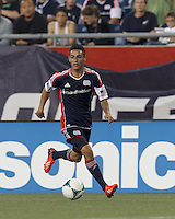 New England Revolution midfielder Diego Fagundez (14) dribbles down the wing. In a Major League Soccer (MLS) match, the New England Revolution (blue) tied D.C. United (white), 0-0, at Gillette Stadium on June 8, 2013.