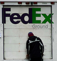 A Fedex worker locks a car in the Manhattan borough of New York. 12/26/2015. FedEx drivers work overtime to deliver packages to customers furious over late Christmas deliveries. photo by VIEWpress