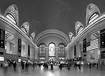 """Hustle n Bustle"" Black and White Panoramic Grand Central Terminal Manhattan New York.  I was very fortunate to be able to schedule an hour on the main floor of the Terminal during such a special year. It was the 100th Year Anniversary for the building.  I wanted to try and capture the light coming through the three windows like in the famous classic old photograph taken when the building was first constructed. When I applied for my photography permit(only one photographer allowed on the floor at a time) I was informed that the light to the windows is blocked by the tall buildings that were added after the Terminal's construction. They did however add the large numbers in the windows to celebrate the 100th Anniversary. I have several photographs that have the ceiling with the constellations in view and the incredible chandeliers that hang in surrounding rooms just off the main floor.  I put my camera on the floor and used my remote to fire the shutter to compose the ceiling with the arches of the windows in view. I also have a couple of panoramic photographs that have transparent travelers in motion moving through and cover the entire width of the main floor."