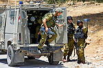 IDF reinforcements deploy from a jeep following a brief clash between soldiers & rock throwing shabab (Palestinian youths) following a nonviolent demonstration against Israel's controversial separation barrier in the West Bank town of Beit Jala near Bethlehem on 27/06/2010.