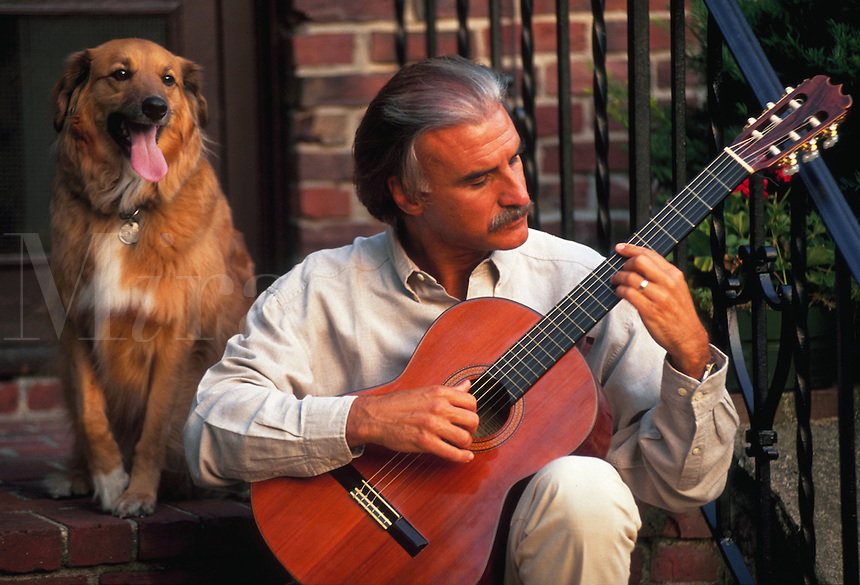 Man playing acoustic guitar on his front steps, kept company by his dog.
