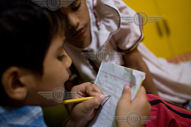 Children from The Naz Care Home do their homework in their rooms at the Care Home. The organisation Naz (meaning Pride) looks after 45 HIV positive orphans and also acts as a drop-in centre for people living with HIV/AIDS.
