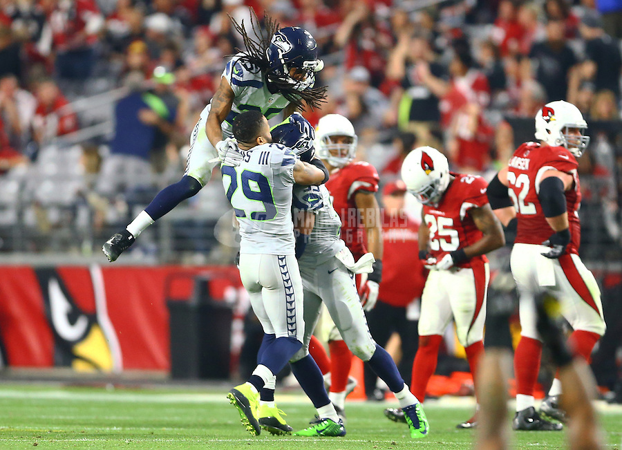 Jan 3, 2016; Glendale, AZ, USA; Seattle Seahawks cornerback Richard Sherman (25) and safety Earl Thomas (29) celebrate as they congratulate safety DeShawn Shead (35) after an interception in the fourth quarter against the Arizona Cardinals at University of Phoenix Stadium. Mandatory Credit: Mark J. Rebilas-USA TODAY Sports