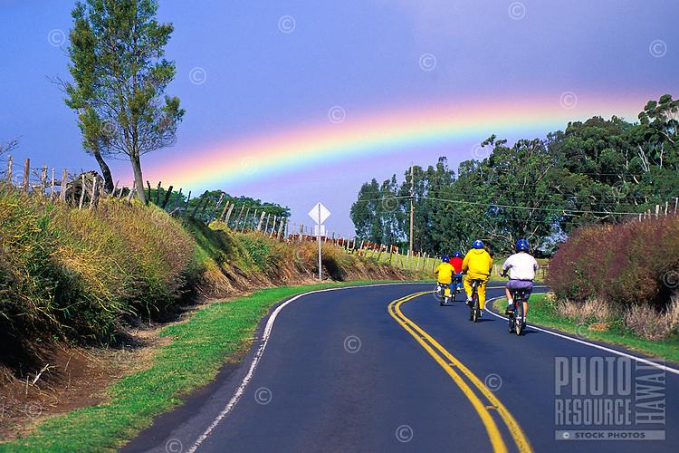 Downhill biking on Haleakala road with rainbow