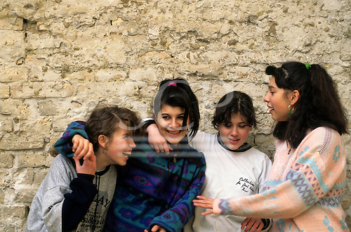 Hungary. Teenage Hungarian female students in front of a brick wall.