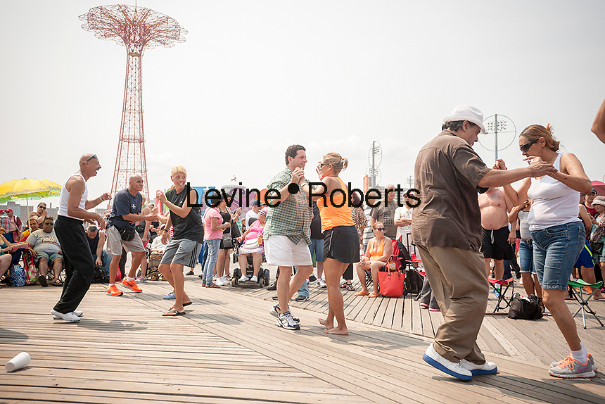 Dancing to salsa on the boardwalk on a seasonably warm Sunday, July 5, 2015 in Coney Island in Brooklyn in New York over the 4th of July weekend. Some of the characters have moved from Times Square to Coney Island because of the increased competition.  (© Richard B. Levine)