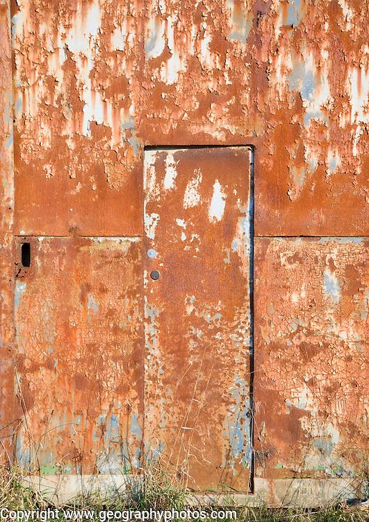 Rusty door on rusted farm barn building, UK