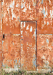 Rusty door on rusted farm barn building, UK
