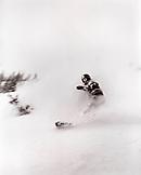CANADA, BC Rockies, Island Lake Lodge, woman snowboarding in the deep powder (B&W)