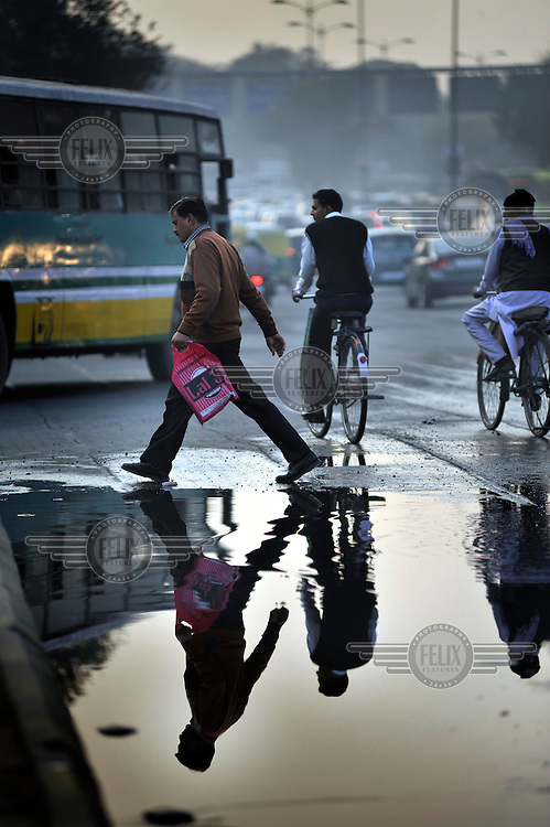 Commuters reflected in a puddle as they make their way home on a busy street in Delhi.