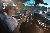 Female driver drinks coffee during daily Austin, Texas commute as sun flares illuminate across the windows.