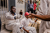 "Workers of the St. Luc Foundation pass around a bottle of rum and cigarettes, during  a collection of abandoned bodies from the premises at Zenith Funeral home - Morgue Privee premises on November 6, 2017 in Port-au-Prince, Haiti. The men step into their white medical overalls, zip them up, and then snap on latex gloves. Some fashion white palls with quilted crosses stitched on them into kerchiefs and wrap them around their heads. Others knot plastic bags around their running shoes. These are their ""blouz mò."" Their death smocks.Then, they unload the coffins, stacking them up at the mouth of a thin alley between two morgues.  The coffins are light — made from cardboard, with thin wooden frames. Soon, they will be heavy.<br /> One worker pulls out a pack of menthol cigarettes and offers them around. Another twists open a mickey of rum, tips back a bracing sip and hands it to the man beside him. It is a bonding ritual, steeling them for the grisly task ahead. <br /> They have come to collect the abandoned dead — men and women whose bodies have lost most distinctive features after weeks or months in the morgue. <br /> Photo Daniel Berehulak for The New York Times"