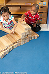 Education Preschool 3-4 year olds boy and girl building together with wooden blocks