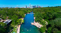 Barton Springs Pool is known as the crown jewel of Austin. From high atop this aerial image shot from a drone provides a view of the crystal clear, emerald green waters of Barton Springs Pool, in the foreground Barton Creek, a free watering hole for those that like to bring their dogs or tip back a few beers or light up a joint and shun Austin's horrific summer heat, and the majestic Austin skyline towering above Zilker Metropolitan Park.