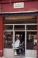 Man getting a haircut in a barbershop or peluqueria in Coyoacan, Mexico City