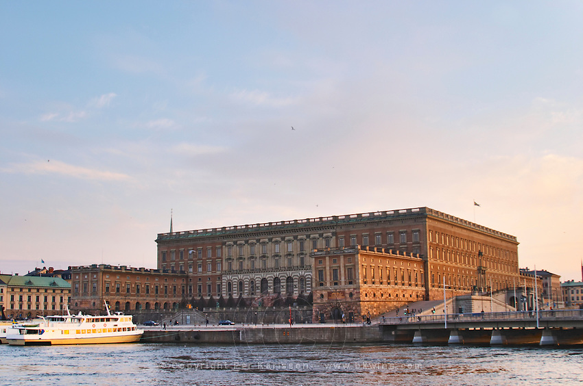 The Swedish Royal Palace in the Gamla Stan, Old Town. In late evening sunshine. White Waxholm boats Waxholmsbatar typical for the archipelago traffic. Stockholm. Sweden, Europe.