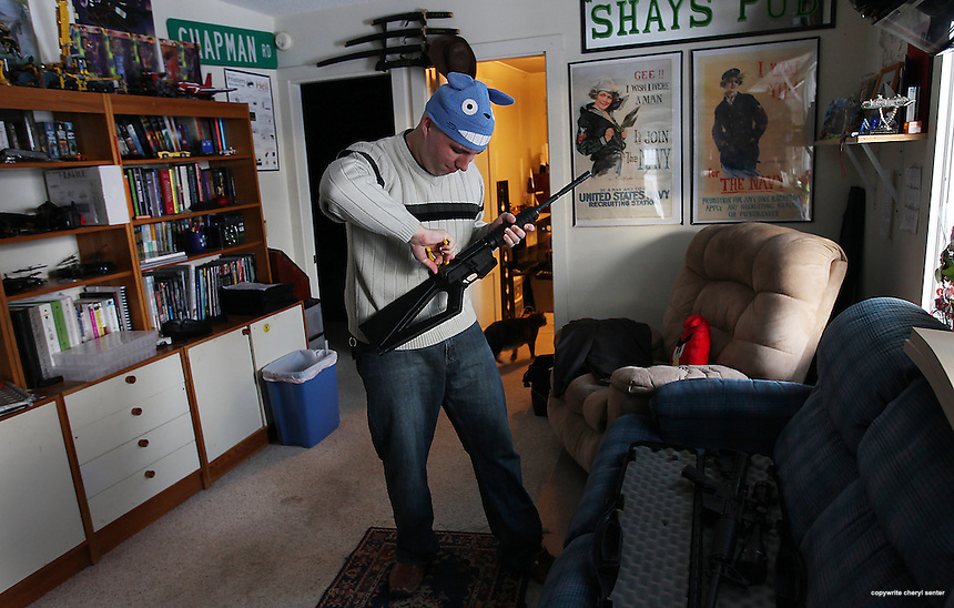 Standing in his Dover, N.H. living room, Chapman Baetzel uses pliers to disassemble his AR 15 rifle that he customized with parts, lower half of rifle, made using a 3D printer, Thursday, Jan. 17, 2013.  (Cheryl Senter for the New York Times)
