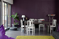 In the dining area one wall is painted a dramatic aubergine in contrast with an acidic green rug on the floor in the adjacent living area