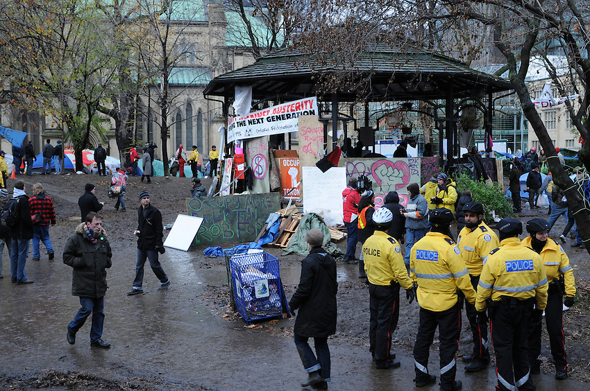 November 23, 2011, Toronto Police deployed in significant numbers this morning, beginning the process of evicting the Occupy Toronto tent camp from St. James Park.  Here, police, media and protesters are seen in the area of the park band shell.