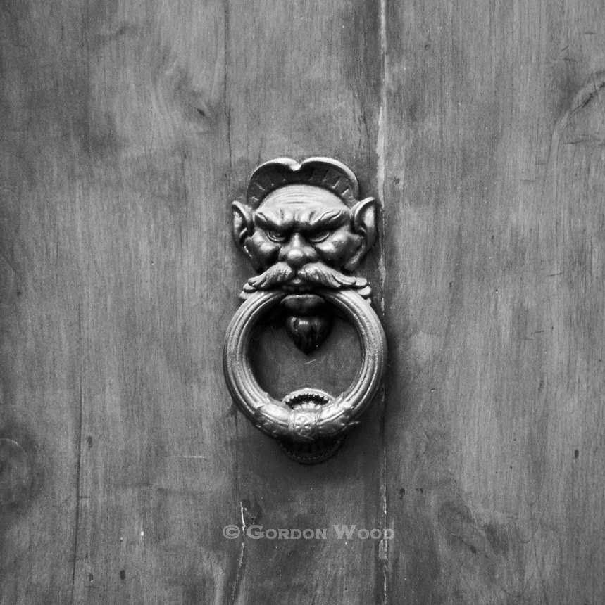 Evil Face Door Knocker on old door in Tuscany Italy