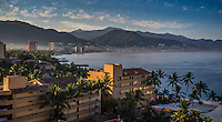 Fine, Art, Landscape, Travel Photograph of a golden sunrise on Banderas Bay in Puerto Vallarta, Mexico. The early morning lighting brings out the colours and textures of the buildings and mountains of this travel scenic.