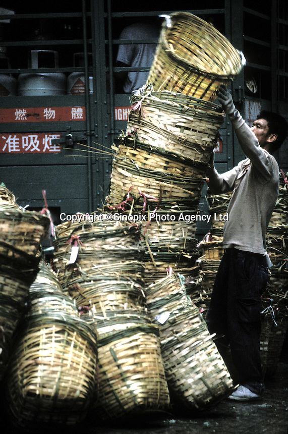 A cleaner with many bamboo baskets in the street of MongKok, Hong Kong.