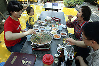 "Korea. South Korea. Incheon. 30 km from Seoul. Family eating dog meat on a saturday lunch in a restaurant specialised with dog food. Incheon. 30 km from Seoul. ""Bosintang"" dish is made of dog meat cooked in a soup with various spices (ginseng, soya,..) and vegetables. On the side, customers will have a choice of diverse plates with pickles, carots, cabbages,... Dog meat is a delicatessen of korean traditionnal cooking. © 2002 Didier Ruef"