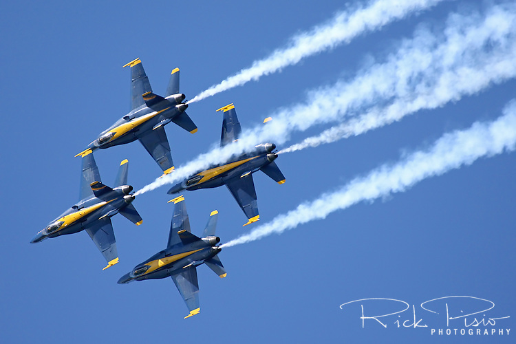 The Blue Angels in diamond formation execute a roll manuever during the 2010 San Francisco Fleet Week Air Show.