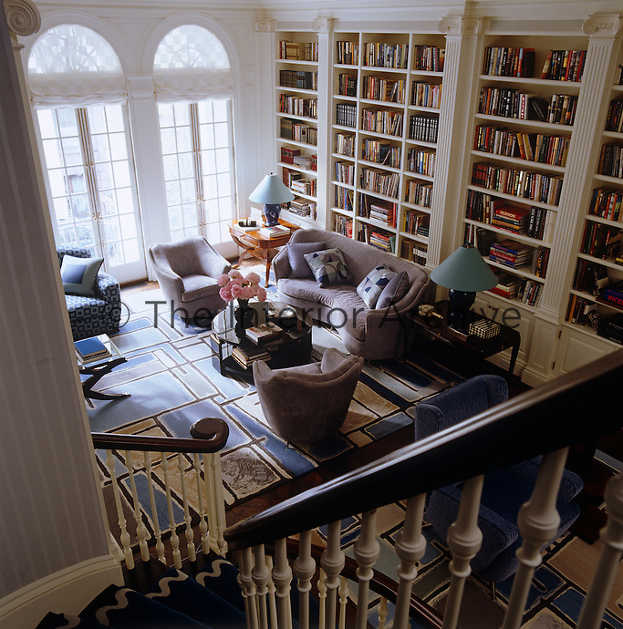 Looking down the stairs into the double-height living room that is dominated by floor-to-ceiling French windows and wall-to-wall bookcases