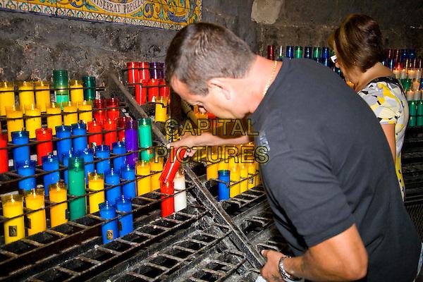 Worshippers lighting candles inside Montserrat Basilica, Montserrat, near Barcelona, Spain