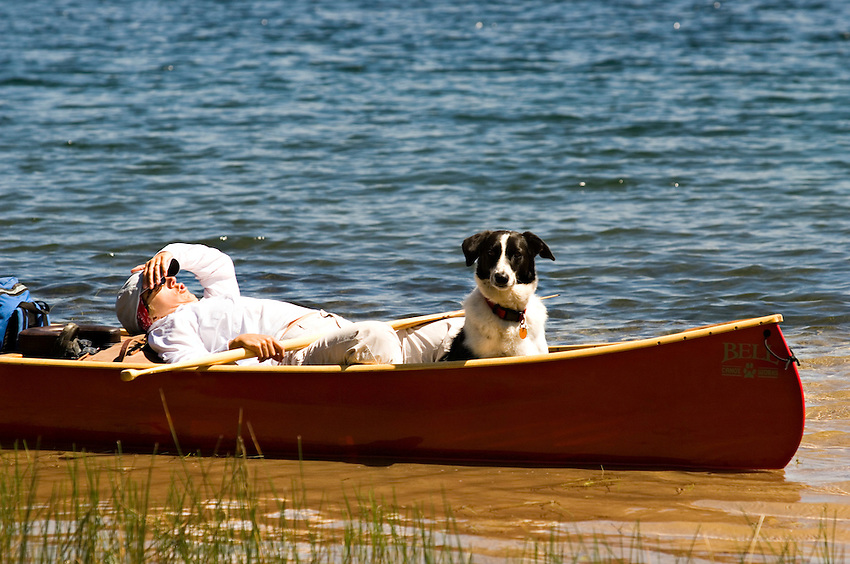 A canoeist and her dog relax in a red canoe at Clark Lake at Sylvania Wilderness Area of Ottawa National Forest near Watersmeet Michigan.