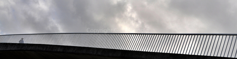 A man walks across the pedestrian bridge over Bayswater Road in the inner Sydney suburb of Rushcutters Bay.