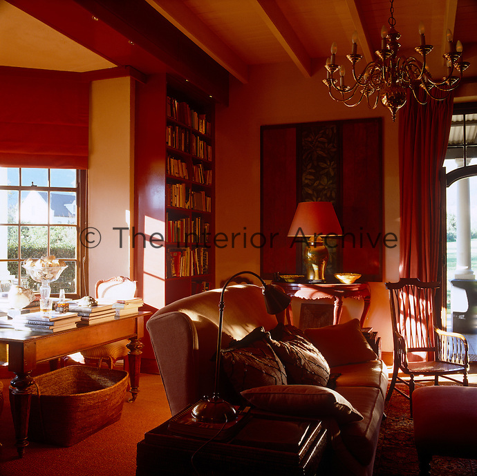 The comfortable study is furnished with a reading table in the bay window and a generous sofa