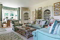 A cream sitting room with green soft furnishings, including two needlework dog cushions