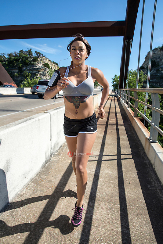 Young african-american woman running and performing endurance marathon work out on the 360 Bridge on Lake Austin, Texas.