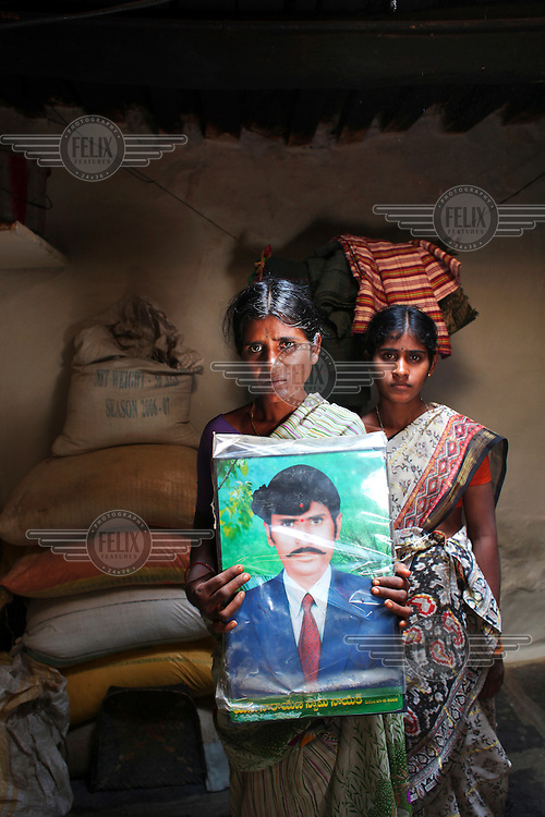 """41 year old Sugali Nagamma stands with her daughter and a portrait of her late husband Mr Narayanaswamy Naik at her home in the village of Kapiripalli in the Anantapur district of Andhra Pradesh. Her husband, a farmer, committed suicide three months ago, after the worst drought this region has experienced in two decades. """"That day he was in a heavy depression, he bought a tin of pesticide and started drinking from it. I tried to take it away from him, but he died in front of us."""" The family have had to borrow money over the last five years due to successive crop failures. Sugali has five children (pictured with her eldest daughter Rathnamma, 22) and has had to take four of them out of school to work in the fields to begin to pay off the debts. """"I'm crying inside, I have no support from anyone."""""""