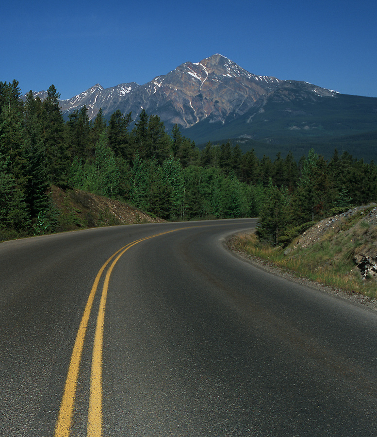 A clear, warm day along a curvy road with Pyramid Mountain in the background in Jasper National Park, Alberta Canada.