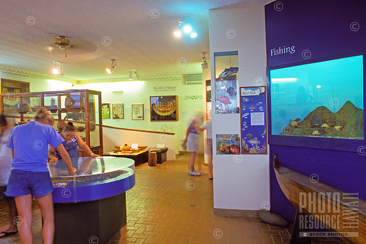Tourists view exhibits at Kauai Museum in Lihue.  The museum showcases Kauai history and artifacts from earliest times to the present