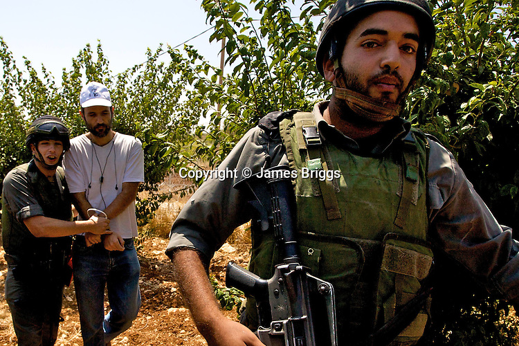 An Israeli activist is arrested by border police officers during a non-violent demonstration in the West Bank village of Beit Ummar near Hebron on 10/07/2010.